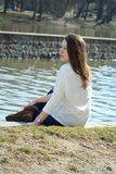 Moça bonita que relaxa próximo pelo rio e que olha para fora ao Fotografia de Stock