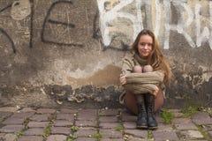 Moça bonita que senta-se no pavimento perto de uma parede de pedra de uma casa Caminhada na cidade imagens de stock