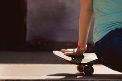 Moça bonita que senta-se no skate Imagens de Stock Royalty Free