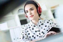 Moça bonita que senta-se nos fones de ouvido na mesa no escritório Foto com profundidade de campo, foco na menina fotos de stock