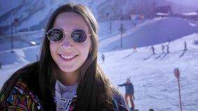Moça bonita que sorri nos óculos de sol no inverno Aprecia o resto da estância de esqui do inverno nas montanhas playfully vídeos de arquivo