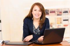Moça bonita que trabalha atrás de uma mesa com Fotografia de Stock Royalty Free