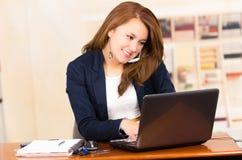 Moça bonita que trabalha atrás de uma mesa com Imagem de Stock Royalty Free