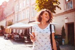 Moça bonita que usa o smartphone e escutando a música que anda na rua Dança da mulher e canto imagem de stock