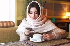 Moça bonita que usa o telefone no café fotografia de stock royalty free