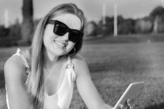 Moça bonita que usa uma tabuleta no parque fotos de stock royalty free