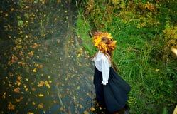 A moça bonita que veste uma grinalda das folhas de outono em uma camisa branca e em uma saia preta entra no rio imagens de stock