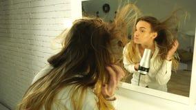 A moça bonita seca o cabelo e olha no espelho video estoque