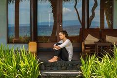 A moça bonita senta na varanda o bungalow perto da praia do oceano na ilha Indonésia de Bali fotos de stock