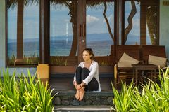 A moça bonita senta na varanda o bungalow na praia Indonésia de Bali fotos de stock