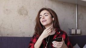 A moça bonita 'sexy' põe fones de ouvido em suas orelhas e começa-os dançar a alguma música Metragem do movimento lento video estoque