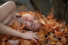 Moça bonita 'sexy' bonita que encontra-se nas folhas de outono douradas, cobertas com as folhas coloridas, com sorriso amigável e fotografia de stock