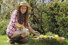 A moça bonita sorri em seu jardim Fotos de Stock Royalty Free