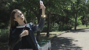 A moça bonita usa o smartphone video estoque