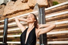 A moça bonita vestiu-se no roupa de banho que toma um chuveiro na praia Foto de Stock Royalty Free