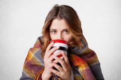 A moça bonito coberta na manta tenta aquecer-se após o passeio durante o dia de inverno frio fora, bebe o café ou o chá quente, i fotografia de stock