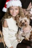A moça bonito com cabelo louro longo e um chapéu de Santa Claus que guarda um cachorrinho produzem o yorkshire terrier que igualm Foto de Stock Royalty Free
