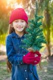 Moça bonito da raça misturada que veste o tampão vermelho e os mitenes da malha que guardam a árvore minúscula fotos de stock