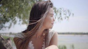 Moça bonito do retrato com o cabelo moreno longo que veste um vestido branco longo da forma do verão que senta-se na margem vídeos de arquivo