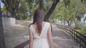 Moça bonito do retrato com os óculos de sol vestindo do cabelo moreno e o vestido branco longo da forma do verão que anda ao long video estoque
