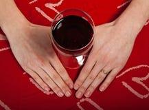 A moça bonito escandinava entrega dar forma a glas de um coração e do vinho Imagens de Stock Royalty Free