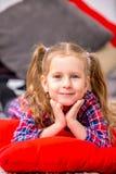 Moça bonito feliz em um vestido azul-vermelho quadriculado que encontra-se na cama e no sorriso fotografia de stock