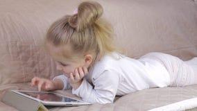 Moça bonito que encontra-se no sofá e que usa uma tabuleta digital Menina com tabuleta em casa vídeos de arquivo