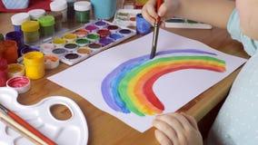 Moça bonito que pinta o arco-íris colorido em casa filme