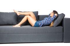 Moça bonito que relaxa no sofá em casa no fundo branco fotos de stock