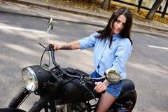 Moça bonito que senta-se em uma motocicleta grande fotografia de stock