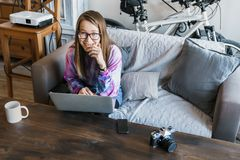 A moça bonito senta-se no computador com vidros e olha-se a câmera e sorri-se modestamente Mulher no computador fotos de stock