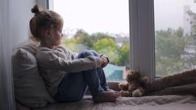 Moça bonito triste que senta-se em um peitoril da janela vídeos de arquivo