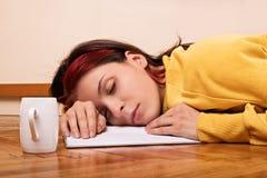A moça caiu adormecido ao aprender imagens de stock
