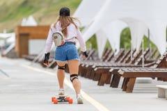 Moça com as almofadas que longboarding perto da praia fotografia de stock