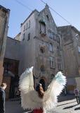 Moça com as asas do anjo em ruas de Lviv fotos de stock