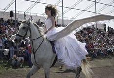 A moça com as asas grandes atrás dela para trás está montando em um cavalo branco Foto de Stock Royalty Free