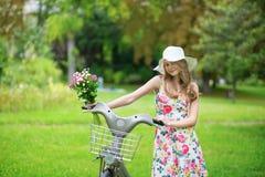 Moça com a bicicleta no campo Imagem de Stock