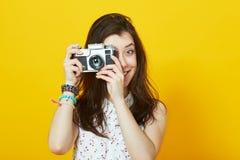 Moça com câmera retro que sorri contra uma parede amarela fotos de stock royalty free