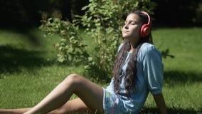 Moça com cabelo escuro longo que escuta a música em fones de ouvido usando uma tabuleta que senta-se na grama em um parque que te vídeos de arquivo