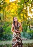 A moça com cabelo longo e em um vestido bonito anda e tem o divertimento exterior fotografia de stock