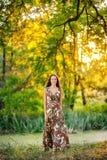 A moça com cabelo longo e em um vestido bonito anda e tem o divertimento no parque fotografia de stock royalty free