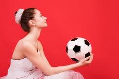 Moça com cabelo longo em um vestido curto com uma bola para jogar o futebol imagem de stock royalty free