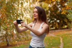 Moça com cabelo longo no parque com telefone celular Fotografia de Stock