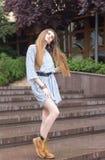 Moça com cabelo longo no vestido curto na cidade Imagem de Stock