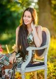 A moça com cabelo longo senta-se em uma cadeira velha bonita no parque imagens de stock royalty free