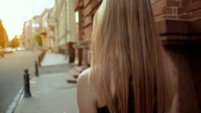 A moça com cabelo louro vai abaixo da rua video estoque