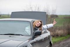 A moça com cabelo luxúria olha fora da janela de carro e rejoic Fotografia de Stock Royalty Free