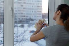 A moça com cuidado lava e limpa uma janela Fotos de Stock