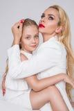 A moça com a filha bonita do os olhos azuis surpreendentes e os bordos vermelhos e cabelo encaracolado louro da mamã dos pregos p Imagem de Stock