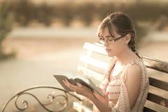 Moça com livro à disposição em um banco Fotografia de Stock